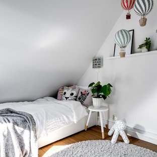 Inspiration för minimalistiska barnrum kombinerat med sovrum, med vita väggar, mellanmörkt trägolv och brunt golv