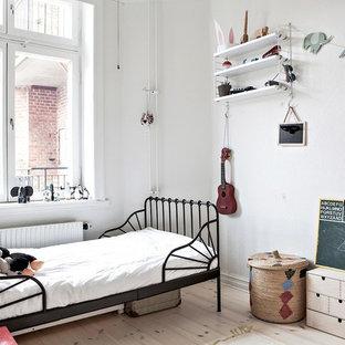 Idéer för ett mellanstort nordiskt könsneutralt barnrum kombinerat med sovrum och för 4-10-åringar, med vita väggar, ljust trägolv och beiget golv