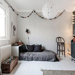 Minimalistisk inredning av ett mellanstort könsneutralt barnrum kombinerat med sovrum, med vita väggar, målat trägolv och vitt golv