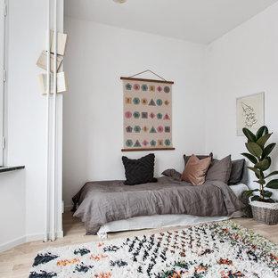 Foto på ett mellanstort minimalistiskt könsneutralt barnrum kombinerat med sovrum och för 4-10-åringar, med vita väggar, beiget golv och ljust trägolv