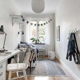 Inspiration för minimalistiska könsneutrala barnrum kombinerat med sovrum, med vita väggar, mellanmörkt trägolv och brunt golv