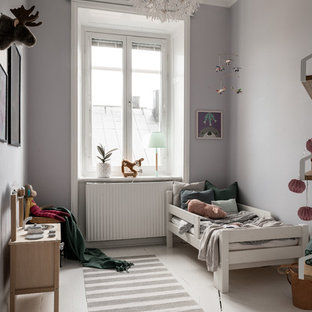 Inredning av ett minimalistiskt könsneutralt småbarnsrum kombinerat med sovrum, med grå väggar, målat trägolv och vitt golv