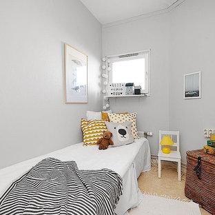 Inredning av ett nordiskt könsneutralt barnrum kombinerat med sovrum och för 4-10-åringar, med grå väggar och beiget golv
