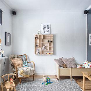 Idéer för att renovera ett mellanstort nordiskt könsneutralt småbarnsrum kombinerat med sovrum, med mellanmörkt trägolv