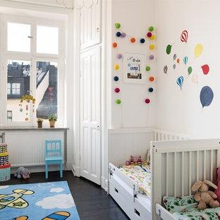 Idéer för att renovera ett mellanstort minimalistiskt könsneutralt barnrum, med vita väggar och mörkt trägolv