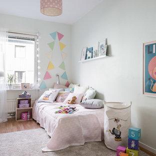Foto på ett mellanstort minimalistiskt barnrum, med vita väggar och ljust trägolv