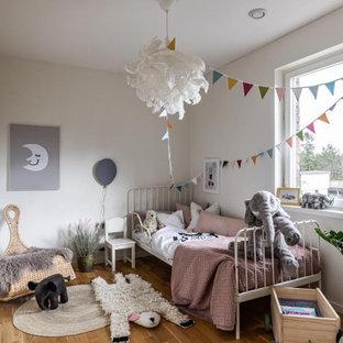 Exempel på ett nordiskt barnrum kombinerat med sovrum, med grå väggar och mellanmörkt trägolv