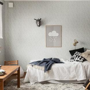 Inredning av ett minimalistiskt könsneutralt barnrum, med grå väggar, mellanmörkt trägolv och grått golv