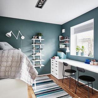 Foto på ett mellanstort minimalistiskt könsneutralt barnrum, med mellanmörkt trägolv, blå väggar och brunt golv