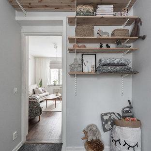 Inspiration för ett litet nordiskt könsneutralt barnrum kombinerat med lekrum, med grå väggar, heltäckningsmatta och grått golv