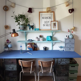 Inredning av ett industriellt stort könsneutralt tonårsrum kombinerat med skrivbord, med vita väggar och ljust trägolv