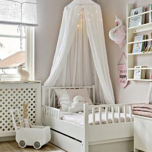 Inspiration för mellanstora minimalistiska könsneutrala barnrum kombinerat med sovrum och för 4-10-åringar, med rosa väggar och ljust trägolv