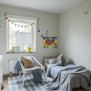 Foto på ett nordiskt könsneutralt barnrum kombinerat med sovrum och för 4-10-åringar, med beige väggar, ljust trägolv och beiget golv
