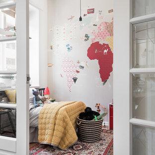 Minimalistisk inredning av ett litet könsneutralt barnrum, med vita väggar och mellanmörkt trägolv