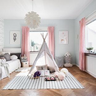 Bild på ett stort skandinaviskt könsneutralt barnrum för 4-10-åringar, med mellanmörkt trägolv och flerfärgade väggar