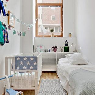 Exempel på ett mellanstort minimalistiskt könsneutralt småbarnsrum, med vita väggar och ljust trägolv