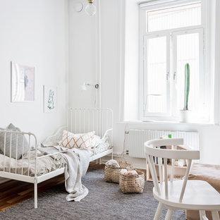 Minimalistisk inredning av ett barnrum kombinerat med sovrum och för 4-10-åringar, med vita väggar, mellanmörkt trägolv och brunt golv