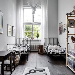 Inspiration för mellanstora minimalistiska könsneutrala barnrum kombinerat med sovrum och för 4-10-åringar, med mörkt trägolv och vita väggar