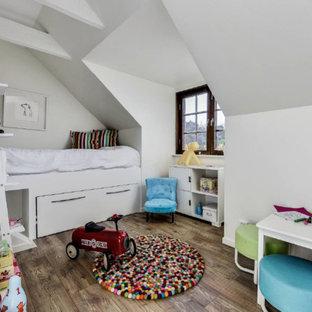 Idéer för ett minimalistiskt könsneutralt barnrum kombinerat med sovrum, med vita väggar, mellanmörkt trägolv och brunt golv