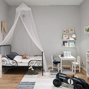 Nordisk inredning av ett mellanstort könsneutralt småbarnsrum, med grå väggar och ljust trägolv