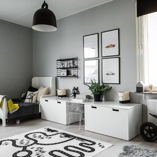 Minimalistisk inredning av ett mellanstort könsneutralt barnrum kombinerat med lekrum och för 4-10-åringar, med grå väggar och ljust trägolv