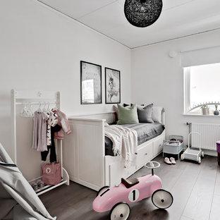 Idéer för ett mellanstort skandinaviskt flickrum kombinerat med sovrum och för 4-10-åringar, med vita väggar, laminatgolv och brunt golv
