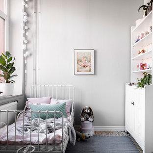 Exempel på ett litet skandinaviskt barnrum, med vita väggar, mellanmörkt trägolv och brunt golv