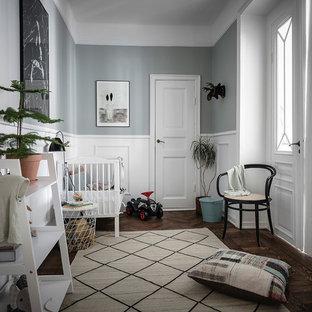 Exempel på ett mellanstort nordiskt könsneutralt småbarnsrum, med grå väggar, mörkt trägolv och brunt golv