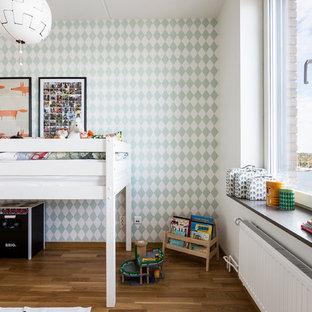 Bild på ett mellanstort skandinaviskt barnrum, med flerfärgade väggar och ljust trägolv