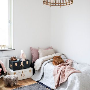 Bild på ett litet minimalistiskt flickrum, med vita väggar, mellanmörkt trägolv och beiget golv