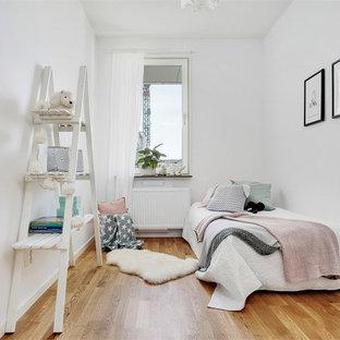 Inredning av ett minimalistiskt flickrum, med vita väggar, mellanmörkt trägolv och brunt golv