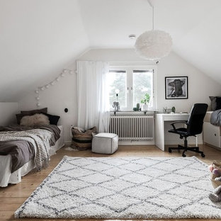 Foto på ett nordiskt könsneutralt tonårsrum, med mellanmörkt trägolv, vita väggar och brunt golv
