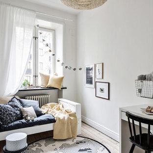Nordisk inredning av ett mellanstort könsneutralt barnrum kombinerat med sovrum och för 4-10-åringar, med vita väggar och ljust trägolv