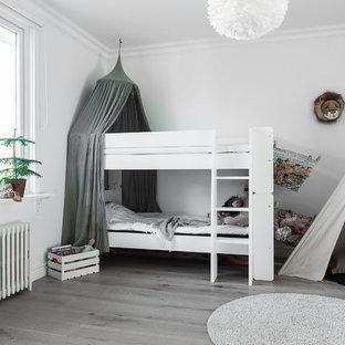 Inspiration för mellanstora skandinaviska könsneutrala barnrum, med vita väggar och ljust trägolv