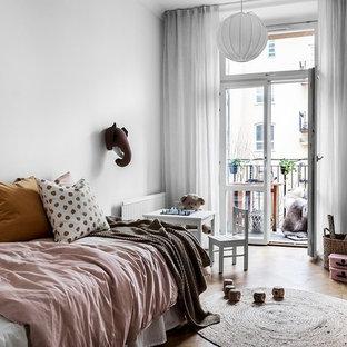Idéer för att renovera ett skandinaviskt flickrum kombinerat med sovrum, med vita väggar, mellanmörkt trägolv och brunt golv