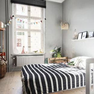 Idéer för ett mellanstort minimalistiskt barnrum, med ljust trägolv