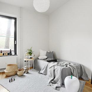 Idéer för att renovera ett nordiskt könsneutralt småbarnsrum, med vita väggar, mellanmörkt trägolv och brunt golv