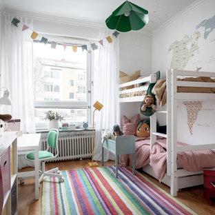 Idéer för att renovera ett nordiskt flickrum, med vita väggar, mellanmörkt trägolv och brunt golv
