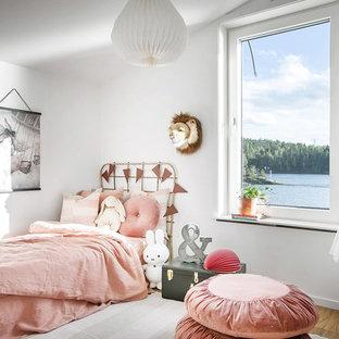 Exempel på ett nordiskt flickrum kombinerat med sovrum och för 4-10-åringar, med vita väggar, mellanmörkt trägolv och brunt golv
