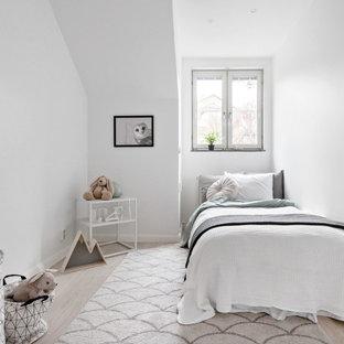 Idéer för ett mellanstort minimalistiskt könsneutralt barnrum kombinerat med sovrum och för 4-10-åringar, med vita väggar, ljust trägolv och beiget golv