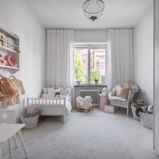 Inredning av ett skandinaviskt flickrum kombinerat med sovrum, med vita väggar, målat trägolv och vitt golv