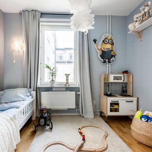 Idéer för ett skandinaviskt barnrum kombinerat med sovrum, med blå väggar, mellanmörkt trägolv och brunt golv