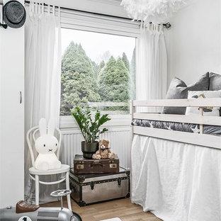 Inspiration för ett litet minimalistiskt barnrum för 4-10-åringar och kombinerat med sovrum, med vita väggar, mellanmörkt trägolv och brunt golv