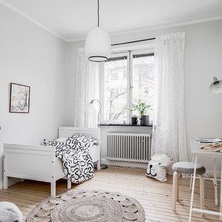 Exempel på ett minimalistiskt könsneutralt barnrum kombinerat med sovrum, med grå väggar, ljust trägolv och beiget golv