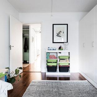 Idéer för ett mellanstort nordiskt könsneutralt småbarnsrum kombinerat med lekrum, med vita väggar och mörkt trägolv