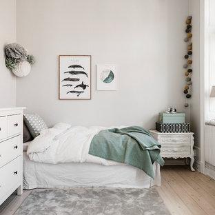 Bild på ett mellanstort skandinaviskt könsneutralt barnrum för 4-10-åringar, med vita väggar, ljust trägolv och beiget golv