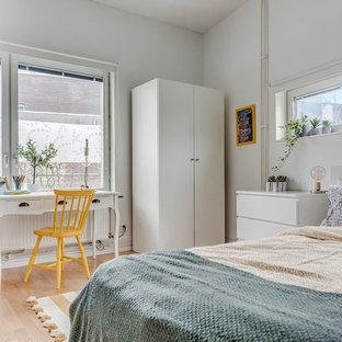 Inredning av ett minimalistiskt barnrum kombinerat med sovrum, med vita väggar, ljust trägolv och beiget golv