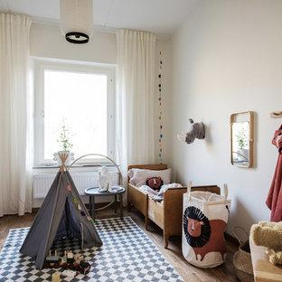 Inspiration för ett skandinaviskt könsneutralt småbarnsrum kombinerat med sovrum, med vita väggar och mellanmörkt trägolv