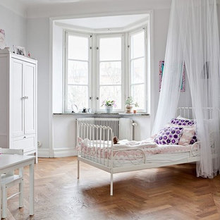 Idéer för ett mellanstort skandinaviskt könsneutralt barnrum kombinerat med sovrum och för 4-10-åringar, med vita väggar och mellanmörkt trägolv