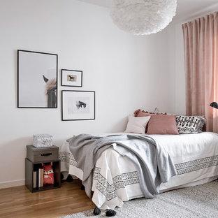 Idéer för mellanstora skandinaviska barnrum, med vita väggar, mellanmörkt trägolv och brunt golv